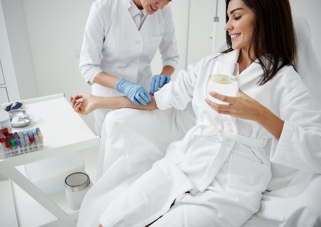 Cropped portrait of beautiful woman in white bathrobe sitting in armchair and receiving IV infusion. She is holding glass of beverage with lemon and smiling