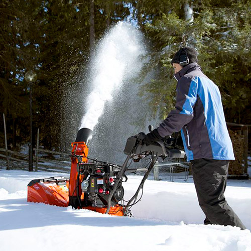 man plowing the snow with a snow thrower