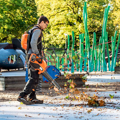 man wearing battery pack attached to leaf blower