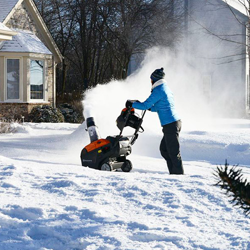 woman plowing snow in cold weather