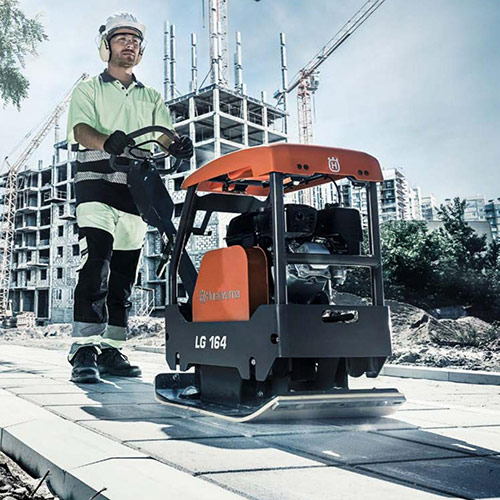 construction man using a plate compactor