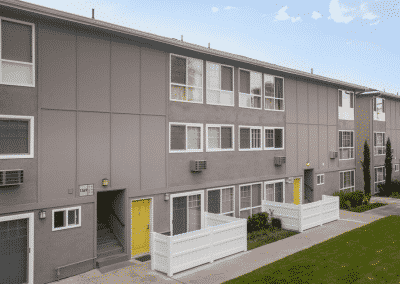 Side of apartment complex showing windows, yellow doors, porches, and grass