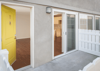 Patio and open yellow door to apartment