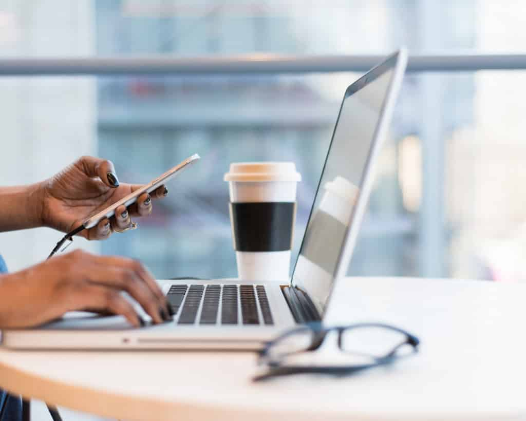 Hands holding phone and typing on laptop with coffee cup and glasses on table