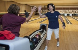 Pauline Fujino, 79, left, of Santa Ana, gives Anne Lastimado, 67, of Tustin, a high-five following her strike early one morning at the Linbrook Bowling Center in Anaheim. Both are members of the Nikkei Seniors bowling group. MARK RIGHTMIRE, THE OC REGISTER