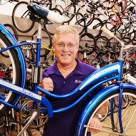 Business photography editorial of a male professional in a purple shirt at a bike shop holding a blue bike.
