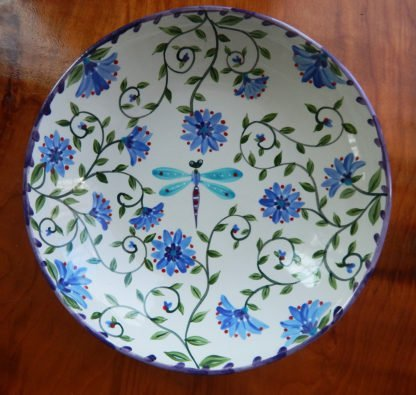 inside serving bowl with a colorful garden motif with a dragonfly