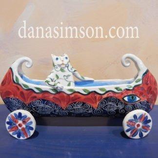 Danasimson.com Cat in canoe on wheels sculpture.