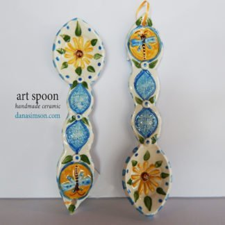Danasimson.com handmade  folk art Dragonfly & Daisy Ceramic Spoon is cut out, formed in clay and individually decorated using my handmade stamps. The raised imagery detail includes a daisy in the spoon area and dragonfly on the handle.