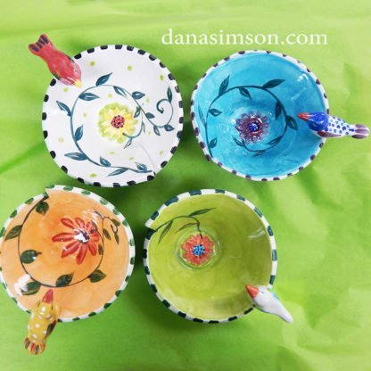 Danasimson.com A set of four different colored Bird Bowls looking down to see the daisy and vine design painted on each interior.