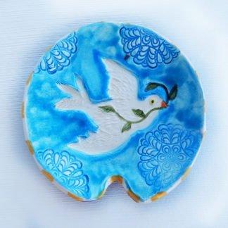 Danasimson.com Handmade ceramic spoon rest with raised image of peace dove.