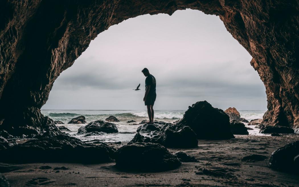 Man standing in pismo beach sea cave