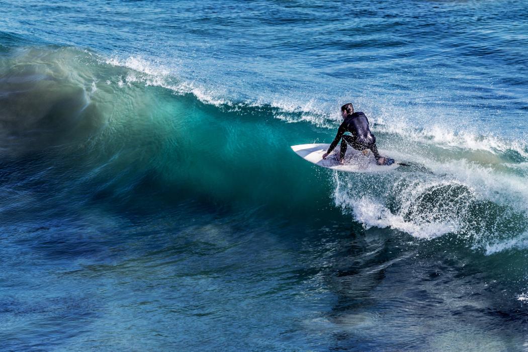 man surfing wave at pismo beach