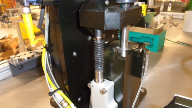 A commercial LVDT is used to verify part height at a high resolution.