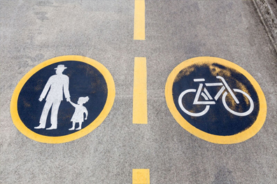 Man with child, and a bicycle painted on a street