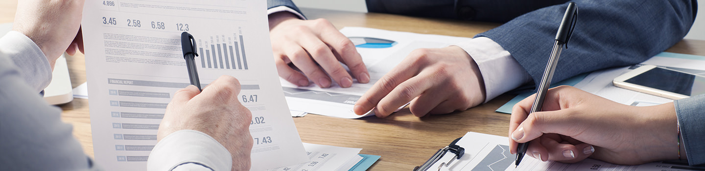 Products & Services Banner Picture - Financial service professional team at work, hands close with business reports and paperwork
