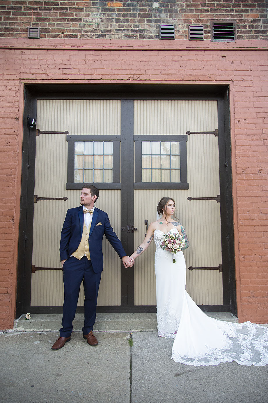 Howell wedding couple poses in front of large doors