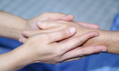 touching hands of asian senior with love and care