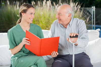 caregiver and senior man looking at each other while reading book