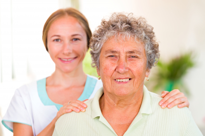 elderly woman with her caregiver in the background