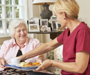 caregiver giving food to senior