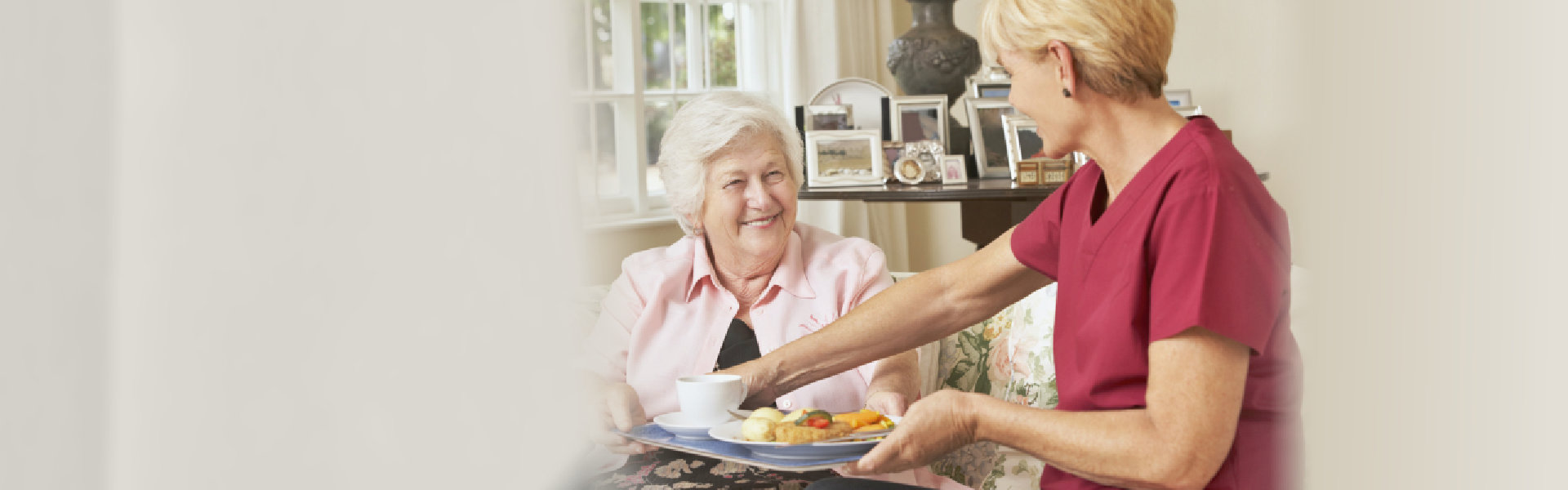 caregiver serving food to senior woman