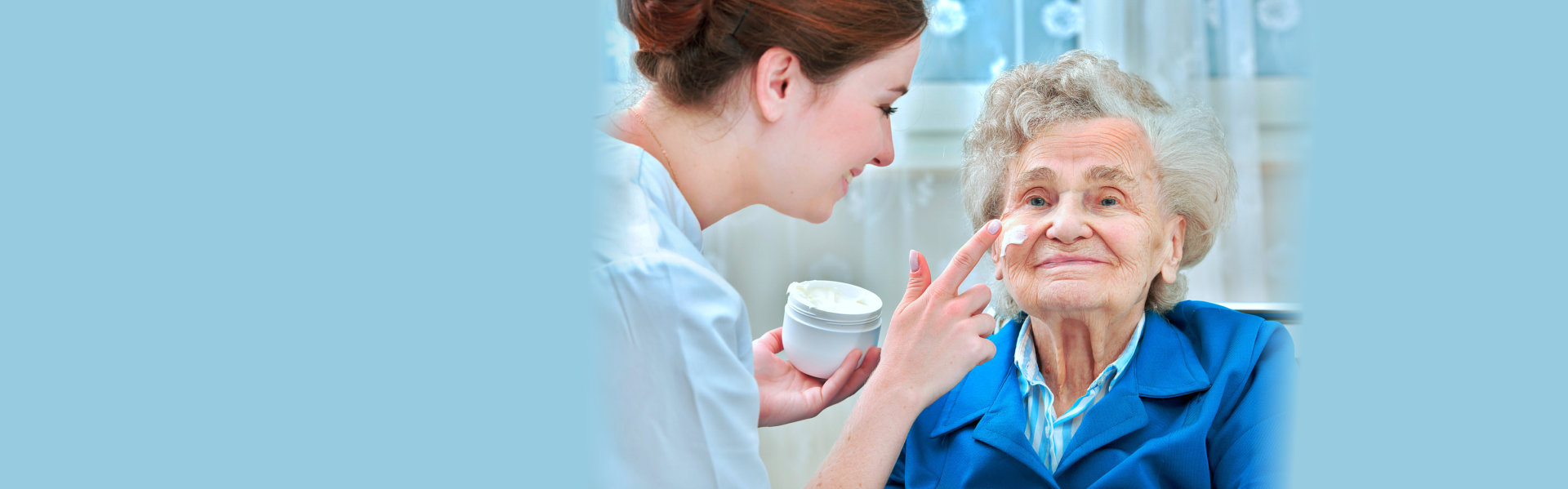 nurse assists an elderly women with skin care