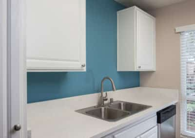 Kitchen with blue walls and white countertops and cabinetry