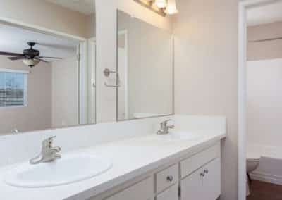 Bathroom with two sinks, white countertops, and cabinets