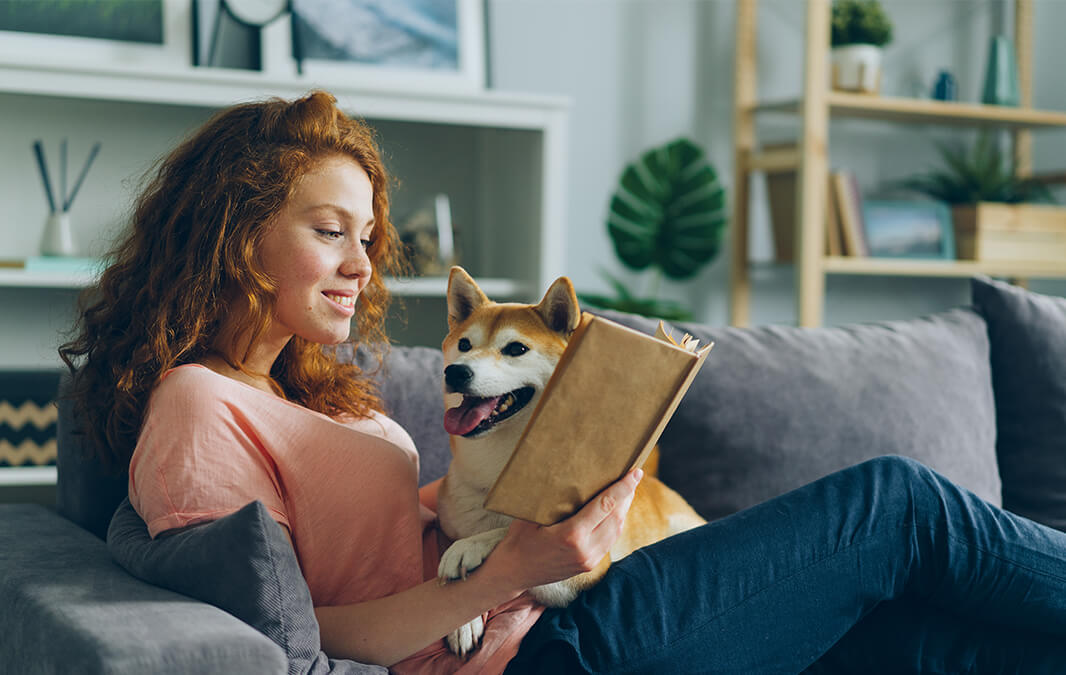 girl reading a book with her dog