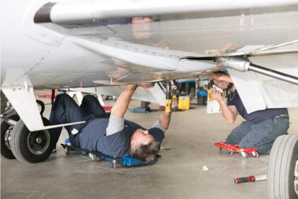 Maintenance Team Working Under Learjet