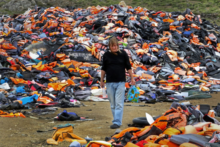 """LESVOS, GREECE (EU) 06-04-2017: Eric Kempson walks through a landfill known as the """"Lifejacket Graveyard,"""" a dumping ground for thousands of discarded life jackets and rubber rafts used by refugees and their smugglers to get to Lesvos, Greece. Eric and his wife Philippa have helped thousands of refugees since the migration crisis began in 2015, and have worked tirelessly to advocate and assist refugees fleeing war-torn Syria and other countries in conflict."""