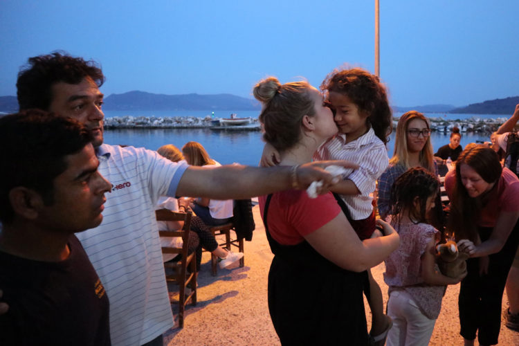 """LESVOS, GREECE (EU)  06/03/2017: Refugees and volunteers from the nearby Moria Refugee camp socialize before dinner at """"Home for All,"""" the Mytileni restaurant that serves dinner each night to refugees for free on the island of Lesvos. A gathering point for donations of goods and emotional support, Home is run by restaurant owners Nikos and Katerina Katsouris, and has become an important gathering point for donations of goods and emotional support, for refugees."""