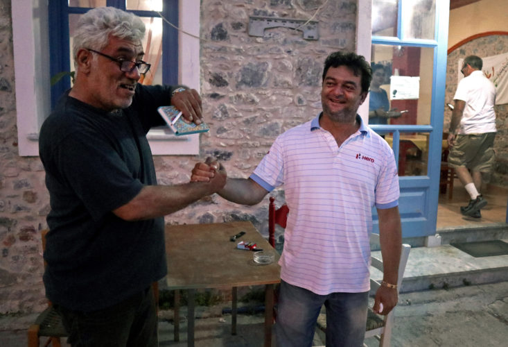 """LESVOS, GREECE (EU)  06/03/2017: """"Home for All"""" Restaurant owner Nikos Katsouris, right, welcomes one of the refugee volunteers to his restaurant. He and his wife Katerina have been serving dinner each night to refugees from the nearby camps since 2014, and they have become a gathering point for donations of goods, classes, WiFi, and emotional support, and has become an integral part of Lesvos's humanitarian reputation during the refugee crisis. Since 2014 they have welcomed refugees to their restaurant, giving them a place to eat and feel like they are home for a day. Home is sustained with help from friends, family, and volunteers who purchase food and offer donations to Nikos and Katerina."""