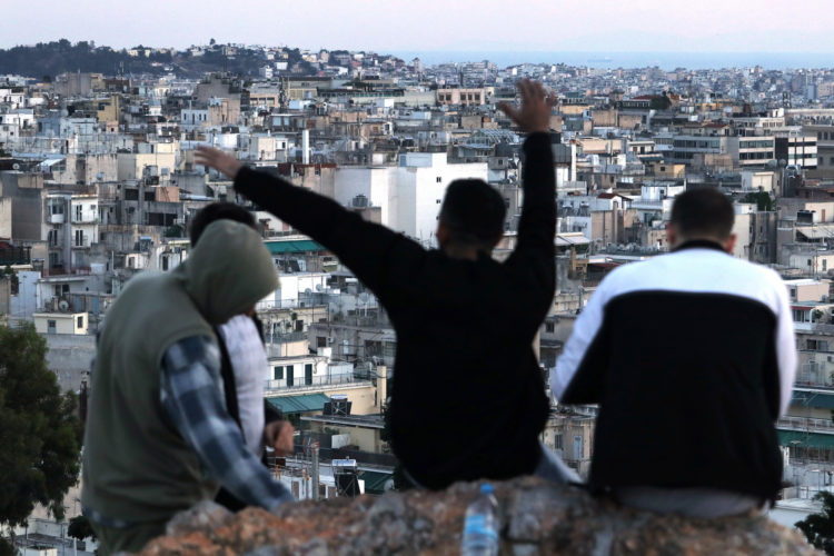 05-30-2017 ATHENS, GREECE (EU): A group of refugees relax on Strefi Hill, a rare rustic green space in the Exarcheia neighborhood of Athens which provides panoramic views stretching over city rooftops to the Acropolis.