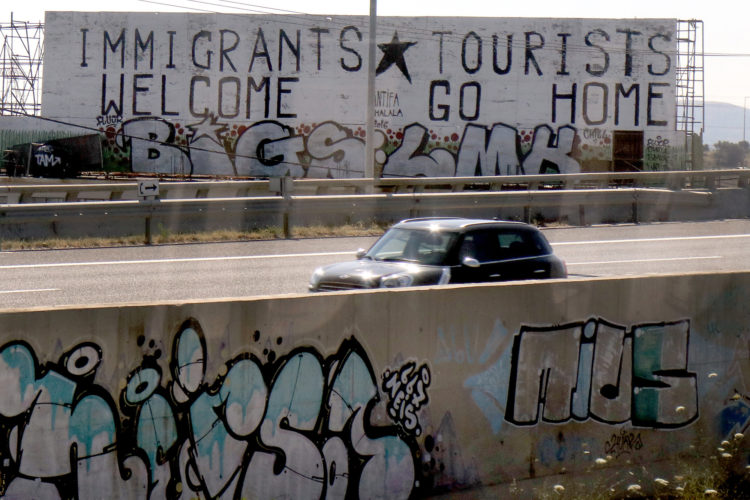 ATHENS, GREECE (EU) 06-10-2017: A pro-immigrant message was spray painted onto a roadside billboard in Athens. As the Syrian refugee crisis continues, nearly 60,000 refugees remain stranded in Greece, according to UNHCR data, and are spread out between three main islands — Lesvos, Chios and Samos — where they face abhorrent conditions, as well as mainland Greece in the cities of Athens and Thessaloniki, where the most environmental damage exists. The influx of nearly 1 million refugees and migrants passing through Greece has had a devastating effect on its environment and economy, particularly during the summers when tourism's high season is in full swing.  The refugee crisis has exacerbated the damage on Greece's already fragile environment, leaving many Greeks worried that tourism — its largest industry — will suffer even more after getting hit hard by the debt crisis that began in 2009.