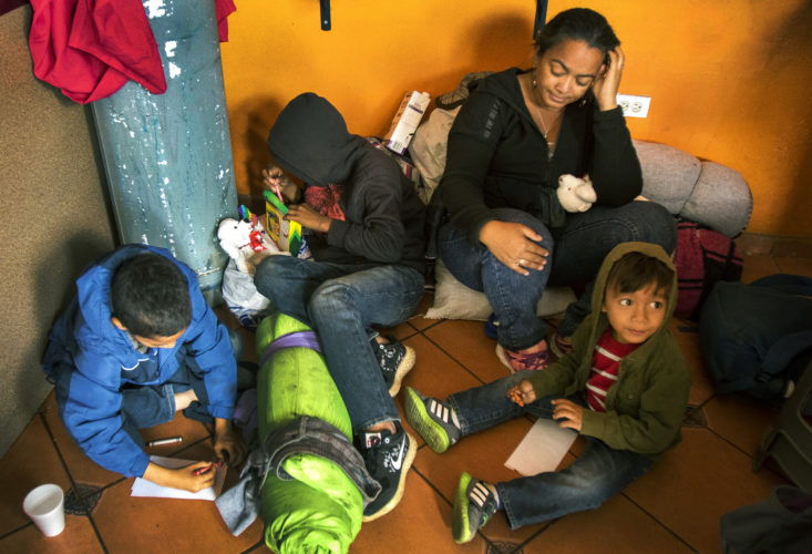 TIJUANA, MEXICO  03-09-2019: Isabela Murillo, with her sons Patric, 12, Jose, 14, and Mateo, 3, of Honduras, sit on the floor of a cafe in Tijuana that offers free food to migrants. Along with her other son Patric, not pictured, they just arrived at the border after traveling for two months in a migrant caravan from Central America. The Border Angels volunteers brought them clean clothes, shoes, and hygiene products then helped them get to the nearby shelter, where they would spend the night before trying to apply for asylum in the U.S.