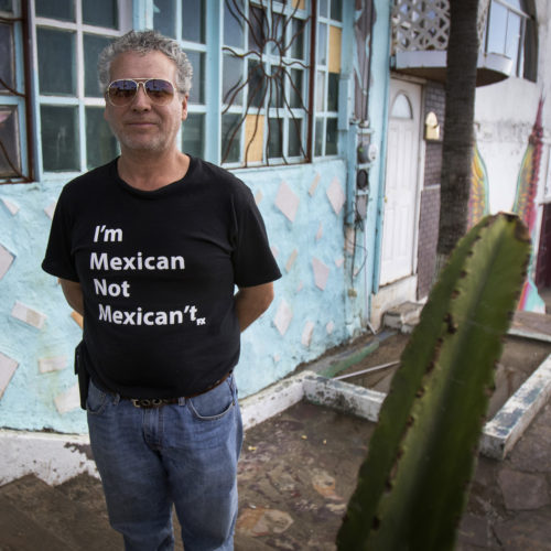 """TIJUANA, CA 03/12/2019:  Border Angels volunteer Miguel Barraza wears a tee shirt wears a """"I'm Mexican, not Mexican't"""" tee shirt outside the office La Playa, in Tijuana. Border Angels is a nonprofit that has been leading humanitarian efforts such as """"water drops"""" in the desert for migrants for over 20-years. In 2019, two border aid volunteers were sentenced to 15 months of probation, must pay fines for dropping off water and food intended for migrants crossing through a protected desert area in southern Arizona."""