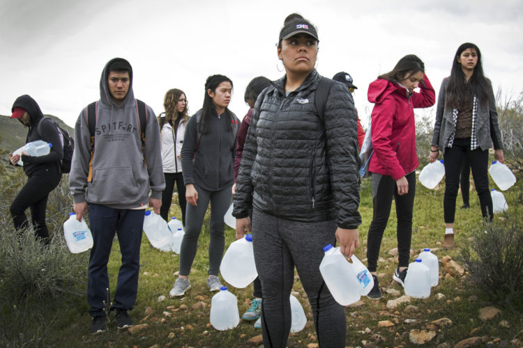 """IMPERIAL COUNTY, CA 03/10/2019:  Joy Kavapalu and other students from University of Utah load up with water bottles as they joined a Border Angels on a  """"water drop"""" in the desert for migrants."""