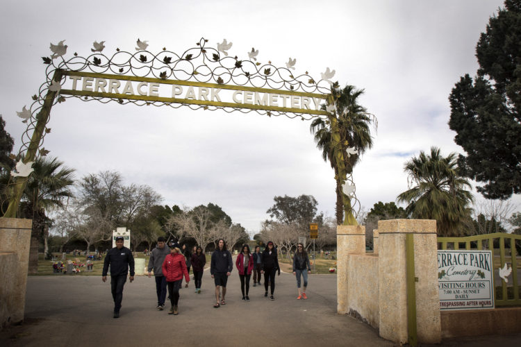 """HOLTVILLE, CA 03/10/2019: Hugo Castro of  Border Angels leads a group of students from the University of Utah into the Terrace Park Cemetery in Holtville, CA, where the """"Cemetery of the Forgotten"""" is hidden in a dirt field behind the cemetery. There, the remains of hundreds of unidentified immigrants are buried in a dirt lot behind the . The unidentified migrants died in the Imperial Valley desert or mountains are buried in anonymity, an extreme reflection of the often desperate attempts by people to enter the U.S. where the flow of unauthorized immigrants has been a source of debate for decades. Hugo Castro and a group students from the University of Utah, who were on a tour of the cemetery and were volunteering for the Border Angels organization, fixed crosses that had fallen over, took photos, and said a group prayer."""