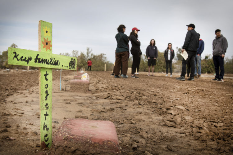 """HOLTVILLE, CA  03-10-2019: Hugo Castro and the volunteers recite a prayer together before leaving the """"Cemetery of the Forgotten,"""" a Potters Field where the remains of hundreds of unidentified immigrants are buried in a dirt lot behind the Terrace Park Cemetery in Holtville, CA."""