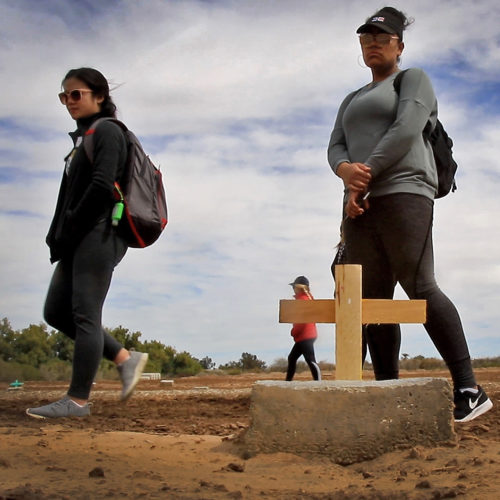 """HOLTVILLE, CA 03/10/2019:  A group of students from the University of Utah visit the """"Cemetery of the Forgotten"""" where the remains of hundreds of unidentified immigrants are buried in a dirt lot behind the Terrace Park Cemetery in Holtville, CA. The unidentified migrants died in the Imperial Valley desert or mountains are buried in anonymity, an extreme reflection of the often desperate attempts by people to enter the U.S. where the flow of unauthorized immigrants has been a source of debate for decades. The students, who were volunteering for the Border Angels organization, fixed crosses that had fallen over, took photos, and said a group prayer with Border Angels' Hugo Castro."""