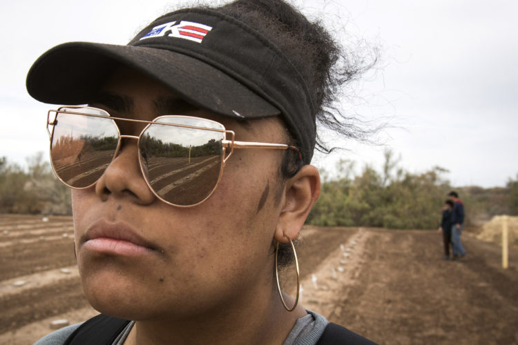 """HOLTVILLE, CA 03/10/2019:  University of Utah student Joy Kavapalu looks at the rows of unmarked graves at the """"Cemetery of the Forgotten"""" where the remains of hundreds of unidentified immigrants are buried in a dirt lot behind the Terrace Park Cemetery in Holtville, CA. The unidentified migrants died in the Imperial Valley desert or mountains are buried in anonymity, an extreme reflection of the often desperate attempts by people to enter the U.S. where the flow of unauthorized immigrants has been a source of debate for decades. Hugo Castro and a group students from the University of Utah, who were on a tour of the cemetery and were volunteering for the Border Angels organization, fixed crosses that had fallen over, took photos, and said a group prayer."""