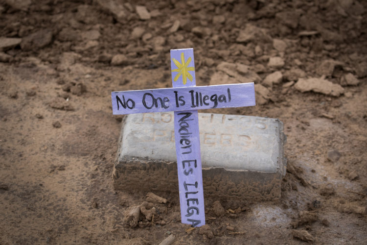 """TIJUANA, MEXICO  03-10-2019: """"No one is illegal"""" says a message on one of the wooden crosses at the """"Cemetery of the Forgotten"""" where the remains of hundreds of unidentified immigrants are buried in a dirt lot behind the Terrace Park Cemetery in Holtville, CA. The unidentified migrants died in the Imperial Valley desert or mountains are buried in anonymity, an extreme reflection of the often desperate attempts by people to enter the U.S. where the flow of unauthorized immigrants has been a source of debate for decades. Hugo Castro and a group students from the University of Utah, who were on a tour of the cemetery and were volunteering for the Border Angels organization, fixed crosses that had fallen over, took photos, and said a group prayer."""