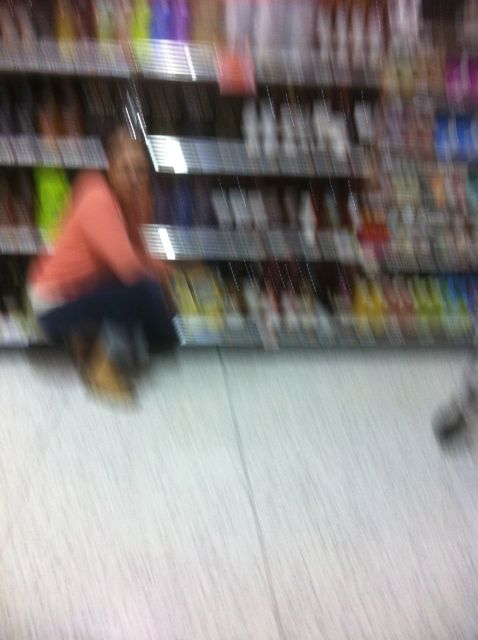 a blurry photo by bucket head of leslie in the wine aisle