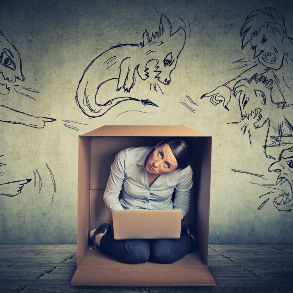 beholdher.life blog no 7 the mother-guilt effect work life balance guilt a woman hiding in a box with angry cartoons pointing and yelling at her