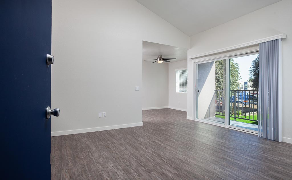 Empty living room with wood floor and ceiling fan