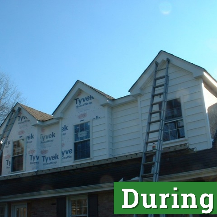 a ladder stretches to the second story of a nearly complete home addition