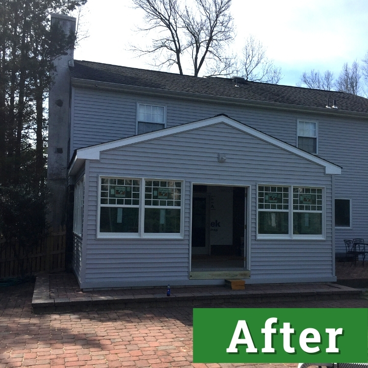 a newly built custom addition on the back of a light grey house