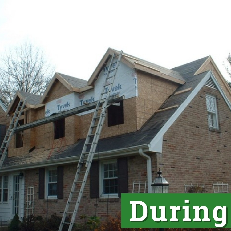 two ladders stretch to the second floor of a newly built home addition